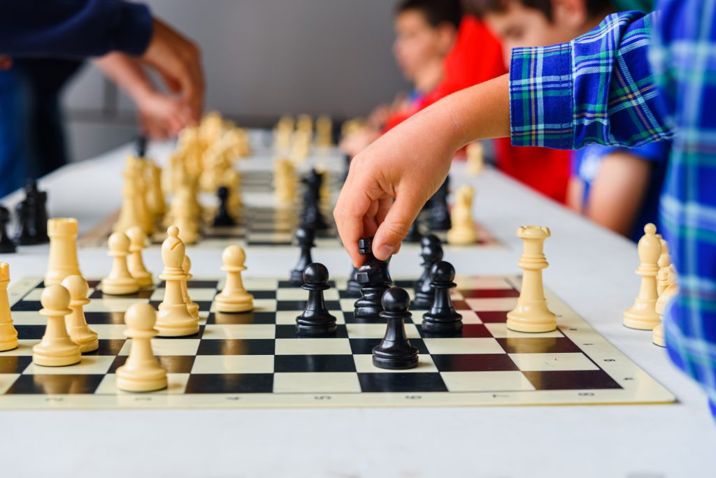 Child's hand moves the horse during a chess tournament with several game boards.